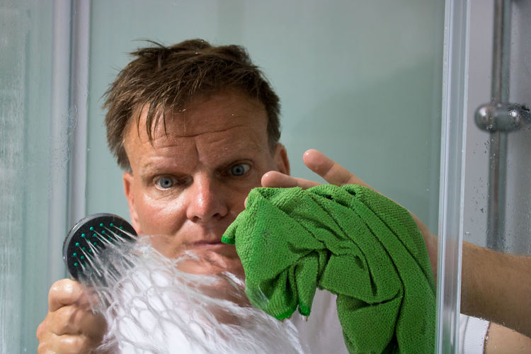 Mature Man Cleaning Bathroom Glass