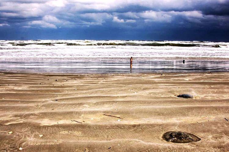 View of sandy beach against cloudy sky