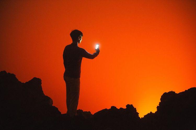 Silhouette Of Woman Using Smartphone Against Orange Sky