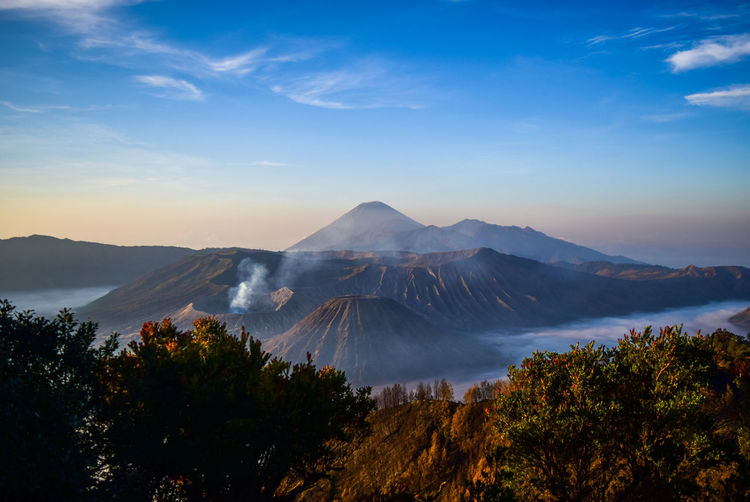Scenic view of volcanoes against blue sky during sunset
