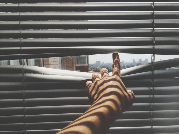 Cropped hand of woman pointing through blinds against sky