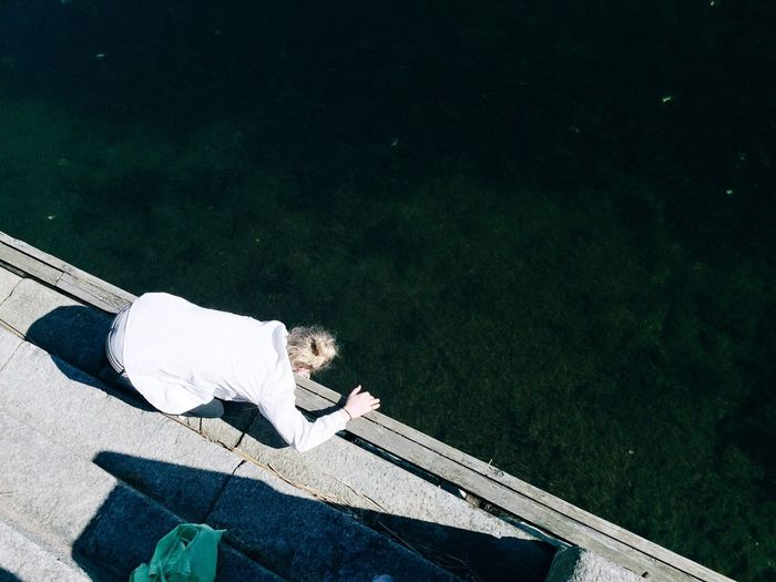 High angle view of woman on pier by sea