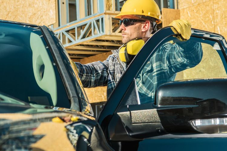 Side view of man working in car