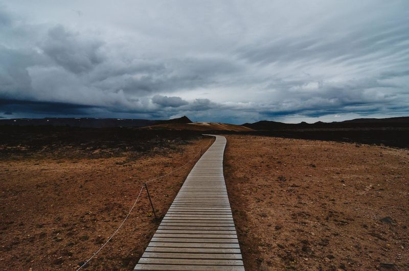 Boardwalk Amidst Field Against Cloudy Sky