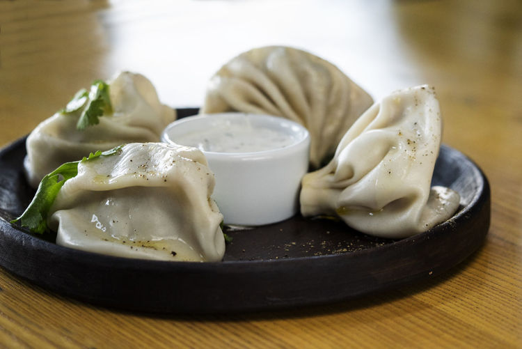 Close-up of khinkali with dip served in plate on wooden table