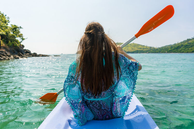 Woman paddling in kayak on the sea around some small tropical islands Canoe Flores Island Freedom Islands Rear View Recreation  Relaxing Sunny Woman Beach Day Kayak Long Hair Ocean Paddle Sea Sport Summer Tropical Vacation Water