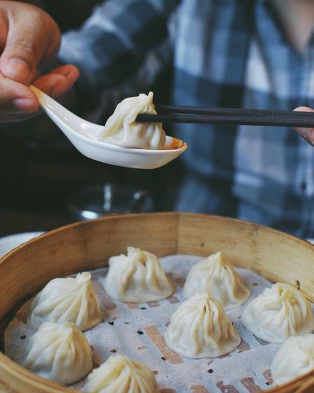 Cropped Image Of Person Holding Dumpling With Chopsticks In Spoon