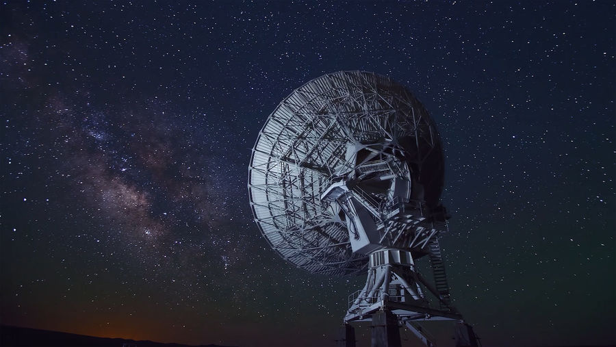 Low angle view of radio telescope against star field at night