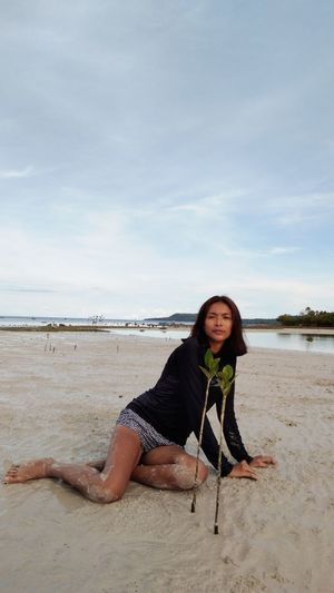 Full length of woman sitting on sand at beach against sky