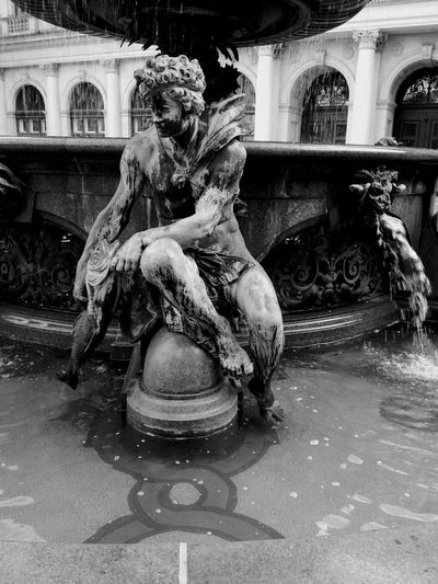 Statue of fountain against building in city