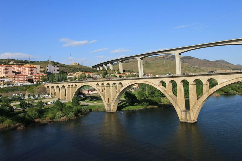 Arch bridge over river against blue sky in city