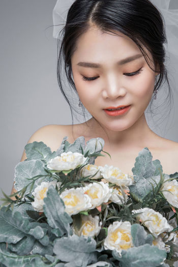 Close-up of woman holding flower bouquet against white background