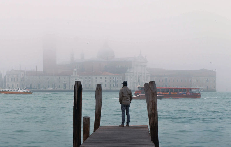 venice italy man standing on the pier near the Grand Canal, cinematic landscape Water Fog Architecture Built Structure Sky Nature Rear View Building Exterior Standing Nautical Vessel Transportation Sea Travel Destinations Real People One Person City Pier Outdoors Looking At View Venice Lonely Cinematic