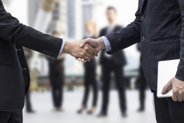 Midsection of well-dressed business colleagues shaking hands while standing in corridor