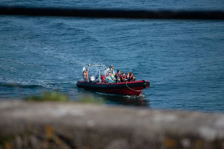 People in boat sailing on sea