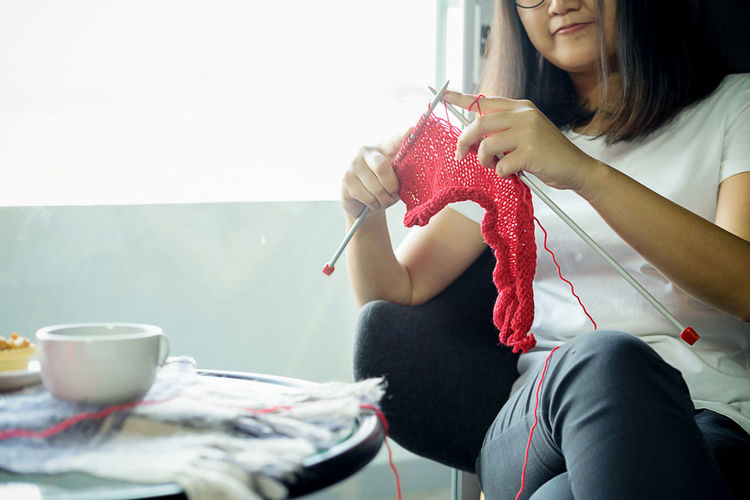 Midsection of woman knitting while sitting at home