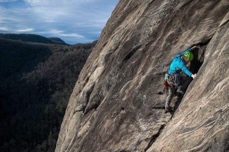 High angle view of man rock climbing against landscape