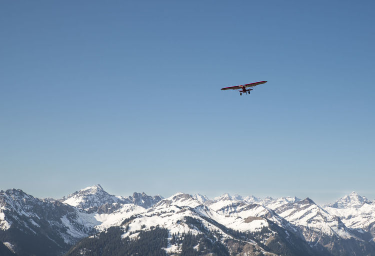 Low angle view of airplane flying over snow covered mountains against clear sky