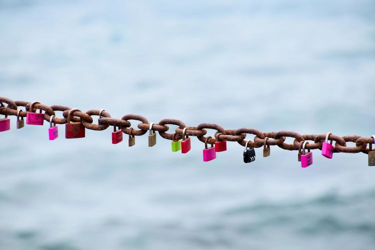 Close-up of padlocks on chain against sky