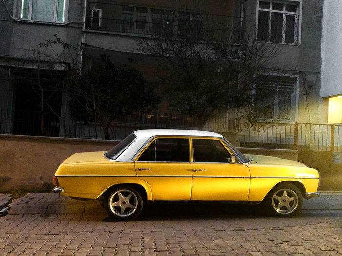 Yellow Car Parked On Street In City