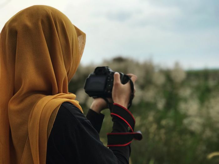 The mustard hijab Malaysia Muslim Moslem Hijab Camera DSLR Female Real People Headshot Leisure Activity Lifestyles Waist Up Holding Focus On Foreground Hood - Clothing Rear View One Person Outdoors Technology Photographing Day Photography Themes