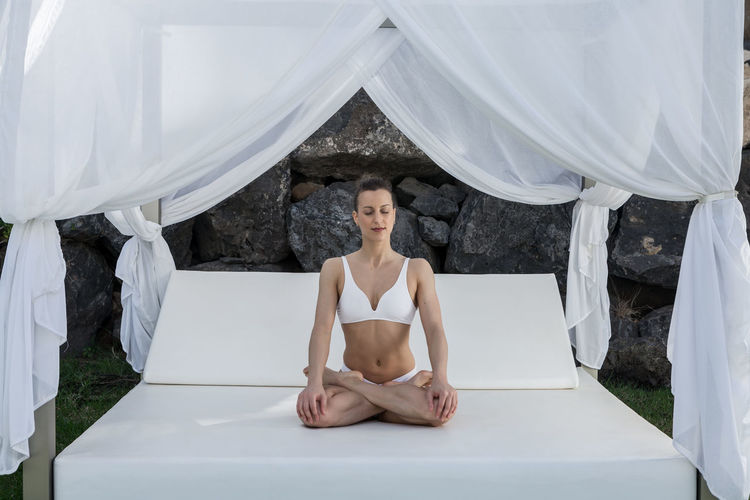 Full length of woman in lingerie meditating while sitting on bed outdoors