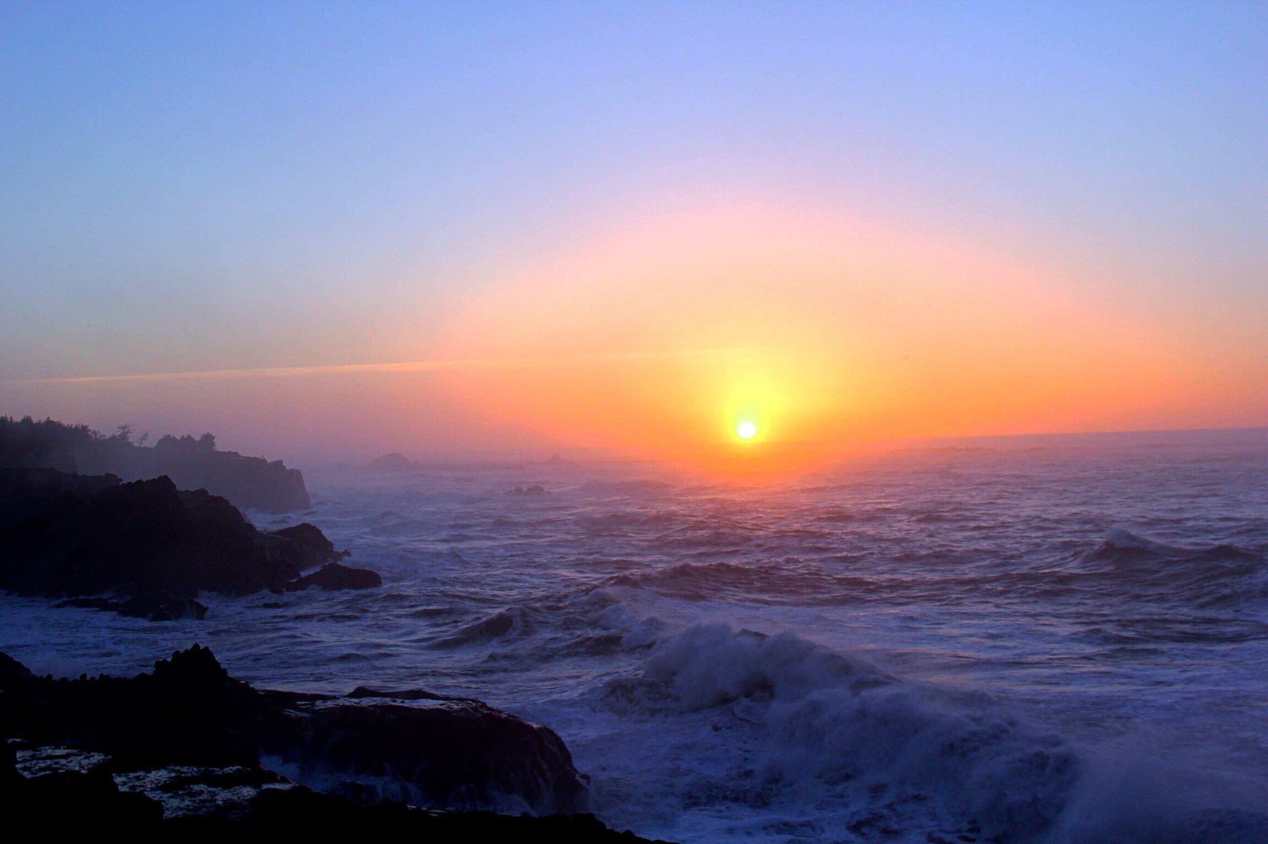 sunset, sea, tranquil scene, beauty in nature, scenics, no people, horizon over water, dramatic sky, nature, rock - object, sky, beach, tranquility, sun, refraction, outdoors, water, landscape, cold temperature, wave, galaxy, astronomy, day