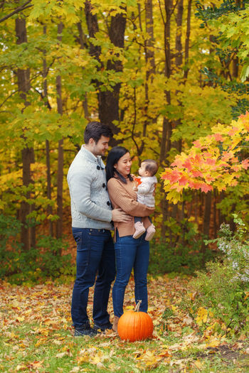 Parents playing with daughter while standing against trees during autumn