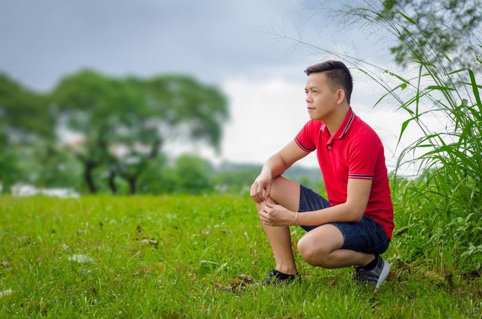 Man in Red! Grass Sitting One Person Full Length Sport Boys Outdoors Leisure Activity Real People Lifestyles Day Tree Sky Athlete Nature Soccer Field red Uniqlo