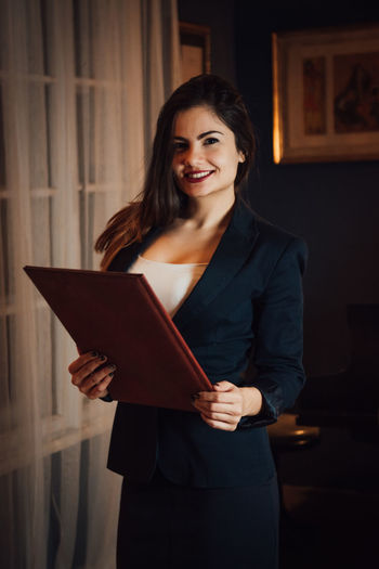 Smiling Standing Holding Indoors  Women Young Adult Front View One Person Waist Up Happiness Looking At Camera Adult Three Quarter Length Young Women Emotion Portrait Real People Home Interior Wireless Technology Beautiful Woman Hairstyle International Women's Day 2019