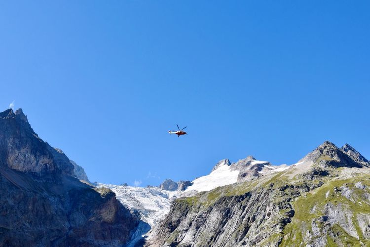 Helicopter in Courmayeur Mountain Blue Low Angle View Flying Mountain Range Rock - Object Nature Clear Sky Day Snow Airplane Scenics Travel Transportation Beauty In Nature Helicopter Outdoors Snowcapped Mountain No People Cold Temperature EyeEm Ready