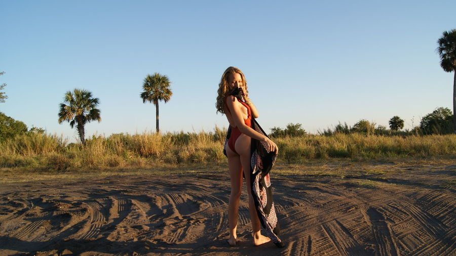 Full length of young woman wearing one piece swimsuit holding scarf on sand
