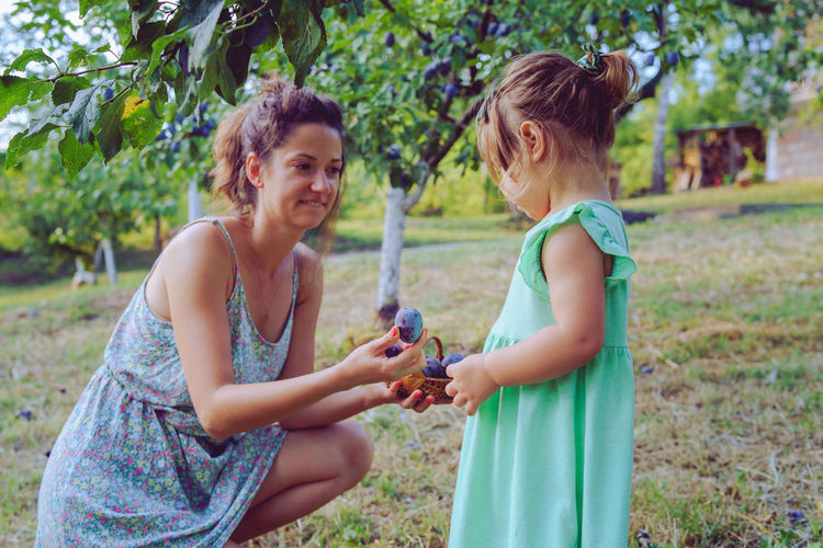 Side view of mother and daughter holding easter eggs on grass