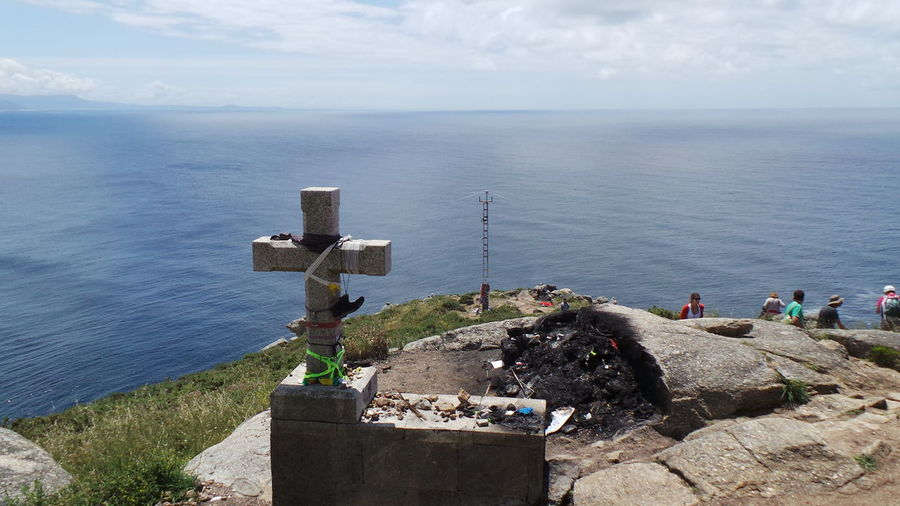 High Angle View Of Cross On Rock Formation By Sea