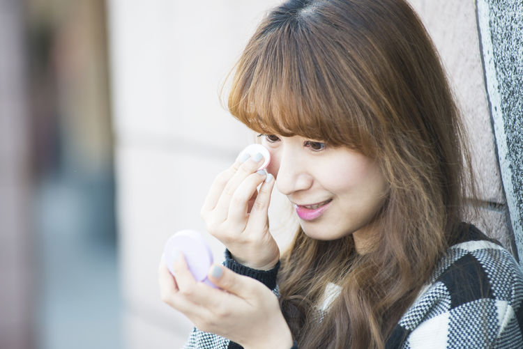 Close-up of woman applying make-up of face