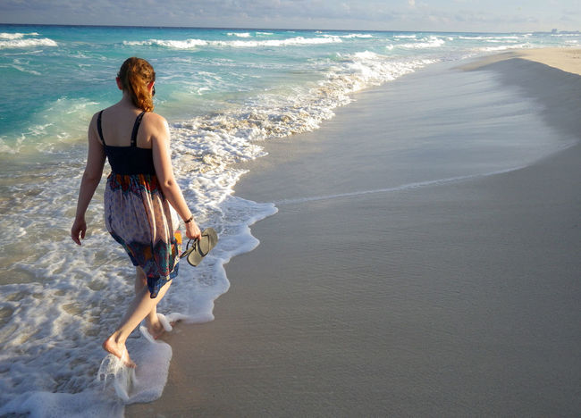 Ankle Deep In Water Beach Beauty In Nature Day Full Length Horizon Over Water Leisure Activity Lifestyles Nature One Person Outdoors Real People Rear View Sand Scenics Sea Shore Standing Sunlight Surf Vacations Water Wave Young Adult Young Women