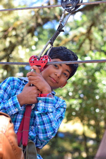 a boy doing adventure Childhood Holding Child Leisure Activity Focus On Foreground One Person Men Tree Real People Boys Day Males  Portrait Lifestyles Nature Outdoors Front View Innocence Adventure