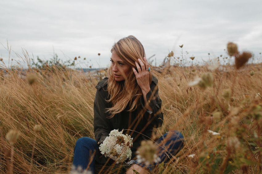 Blond woman sitting in coastal dune grasses on a cloudy day at the beach. Grass Dunes Queen Anne's Lace One Person Land Front View Real People Plant Field Nature Leisure Activity Young Women Women Lifestyles Adult Day Landscape Sky Casual Clothing Hairstyle Outdoors