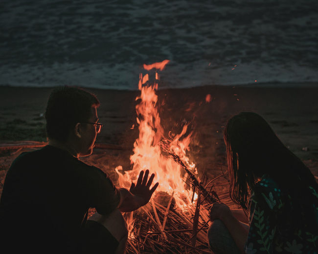 Couple by bonfire at beach during sunset