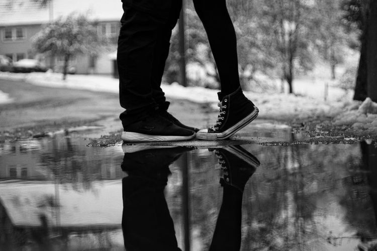 Low section of couple standing by puddle