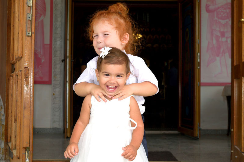 Cute boy strangling sister neck while standing at entrance