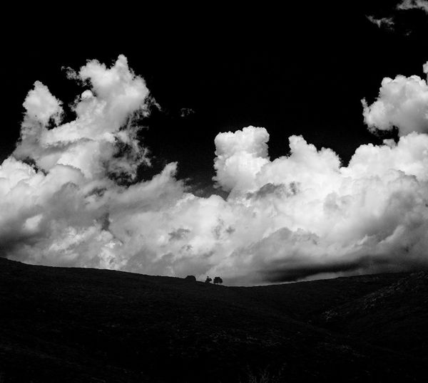 Low angle view of silhouette landscape against sky