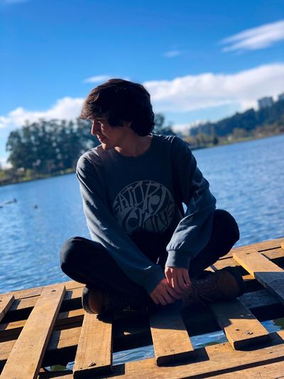 Young man sitting on pier over lake against sky