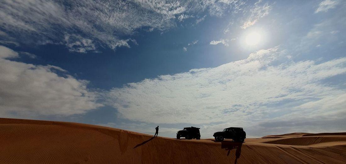 People riding horse in desert against sky