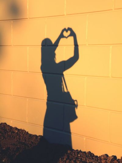 Shadow of woman forming heart on tiled wall