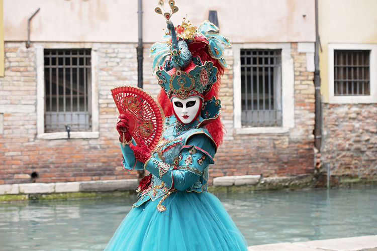 Woman in carnival costume standing by canal in city