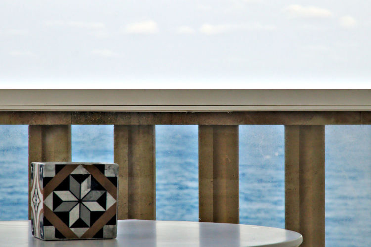 Close-up of table by sea against sky