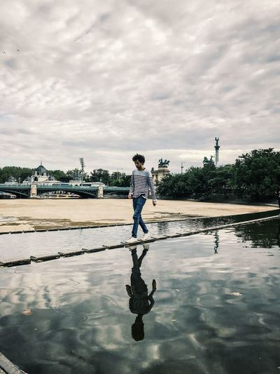 Reflection of man standing in puddle
