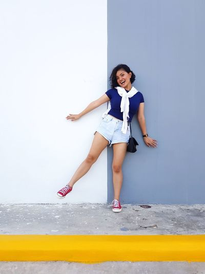 Portrait of happy young woman against wall