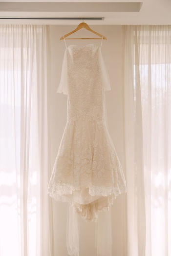 Clothes hanging on white curtain against window at home